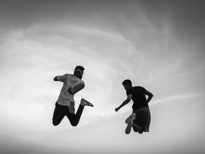 Low Angle View Of Friends Jumping Against Sky