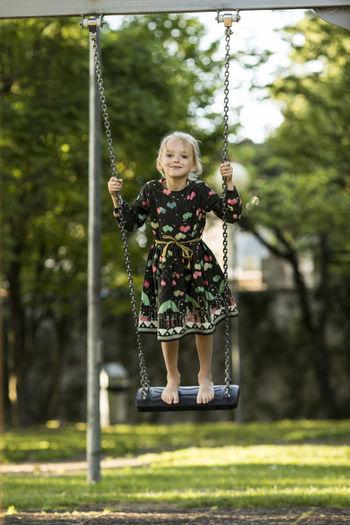 Portrait of smiling girl swinging on swing