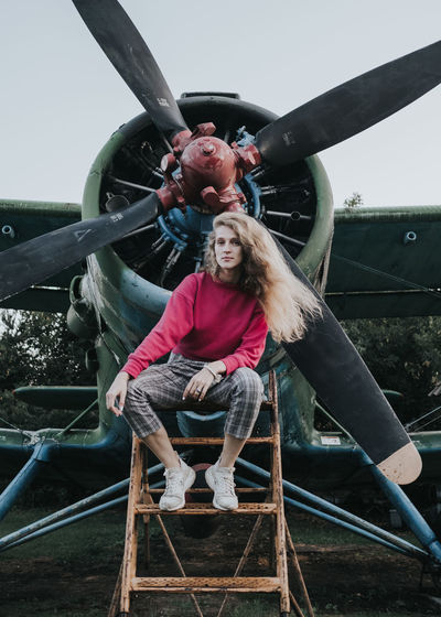 Woman sitting on slide in front of a plane