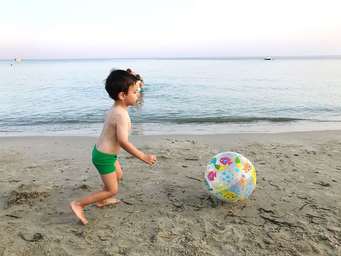 Side view full length of shirtless boy playing with ball on shore at beach