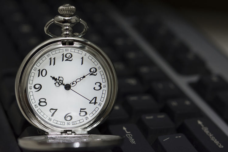 Close-up of pocket watch on computer keyboard