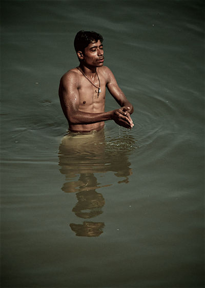 Young man standing in lake