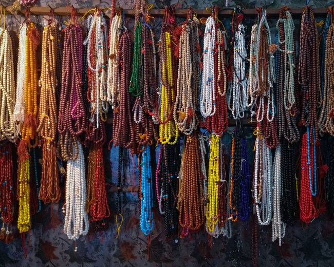 Full frame shot of multi colored prayer beads hanging at market stall