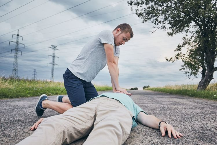 Young man giving cpr to friend lying unconscious on road