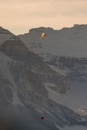 Person hanging from air vehicle against mountain during sunset