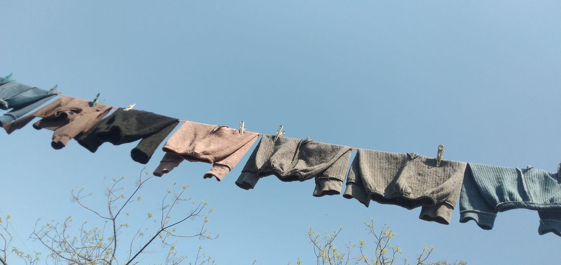 Low angle view of clothes drying on clothesline against clear blue sky