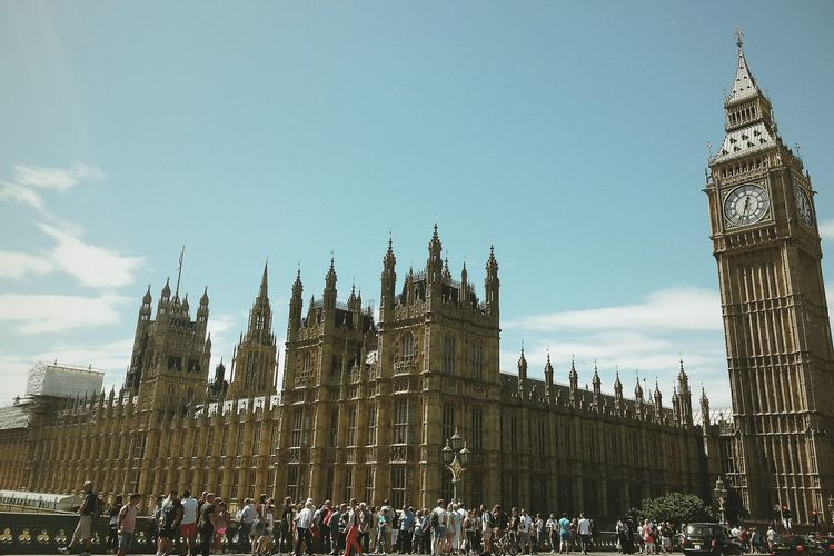 People Walking On Street By Big Ben And Palace Of Westminster Against Sky
