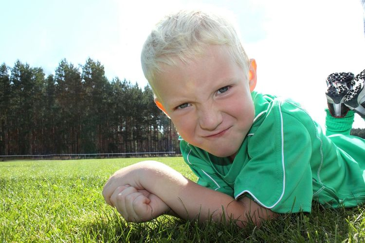 Portrait of boy lying down on field
