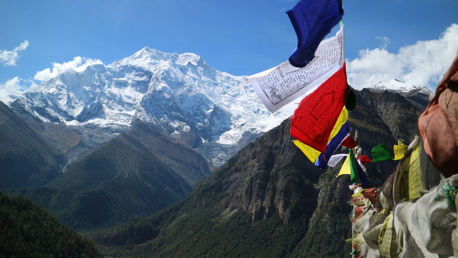 Panoramic view of mountains and flags against sky