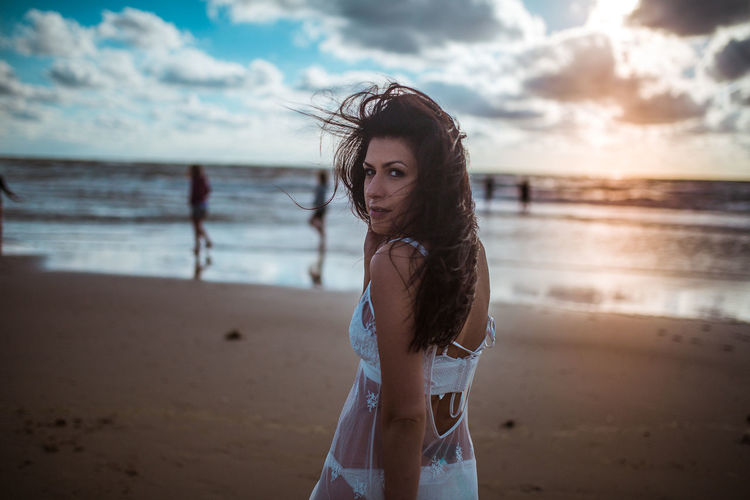 Portrait of young woman standing on beach against sky