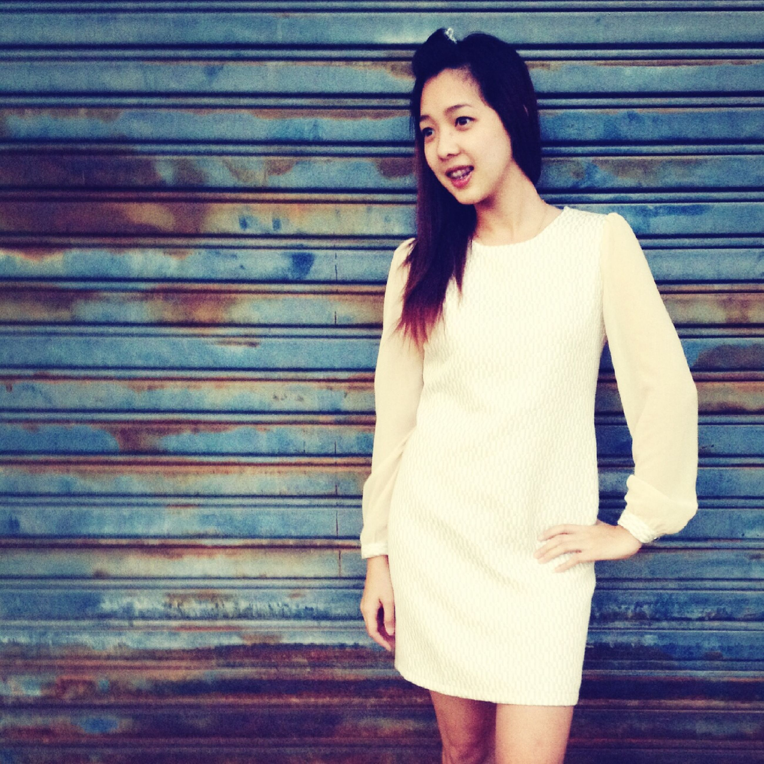 young adult, young women, front view, standing, person, casual clothing, lifestyles, long hair, portrait, looking at camera, three quarter length, leisure activity, fashion, dress, indoors, beauty, wall - building feature