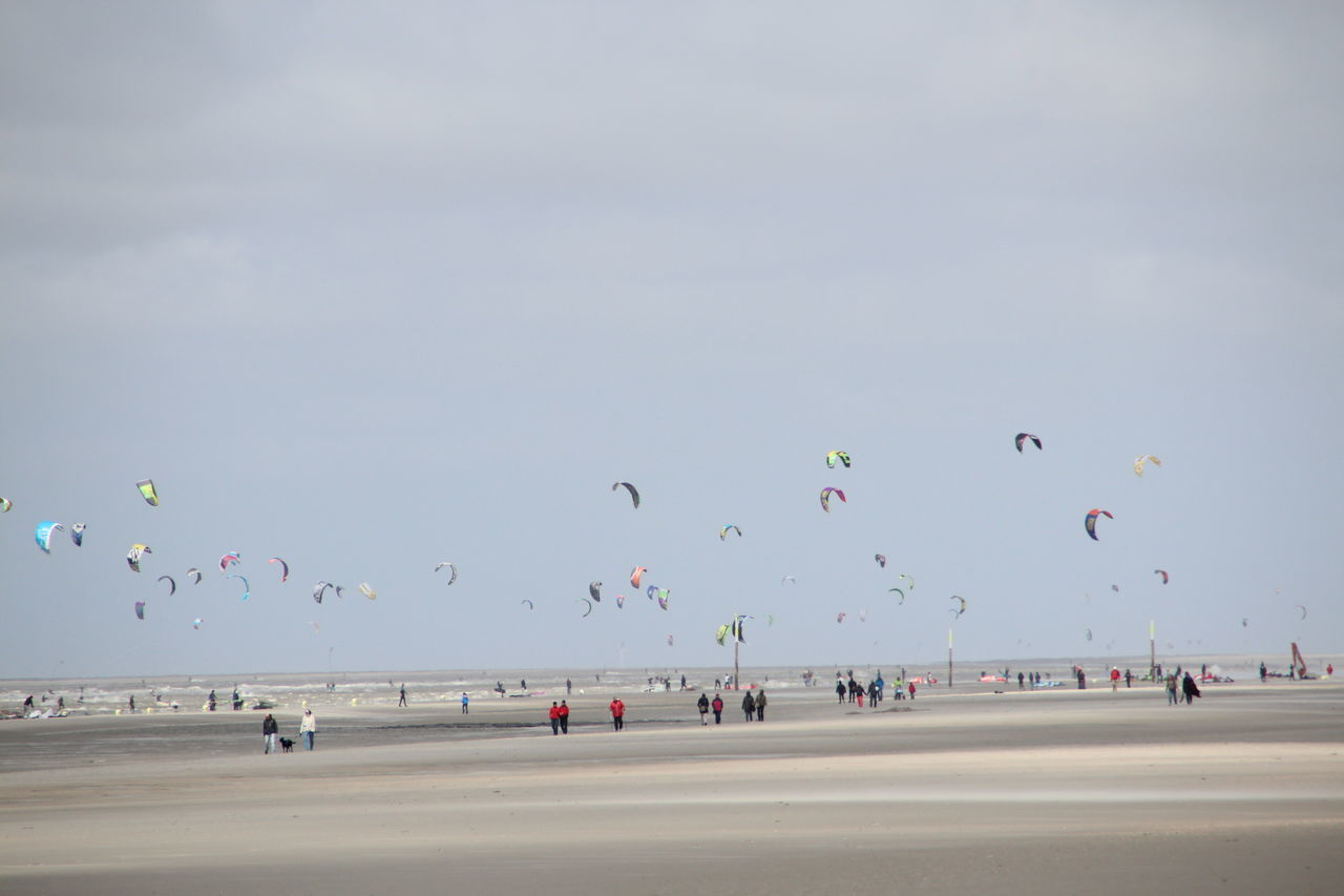 Parachutes At Sandy Beach Against Sky