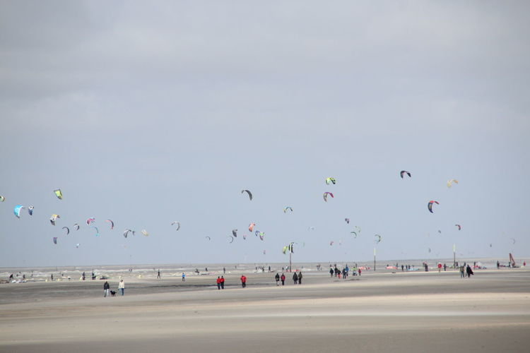Parachutes At Sandy Beach Against Sky