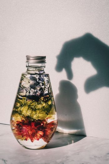 Reflection of person in glass jar on table against wall