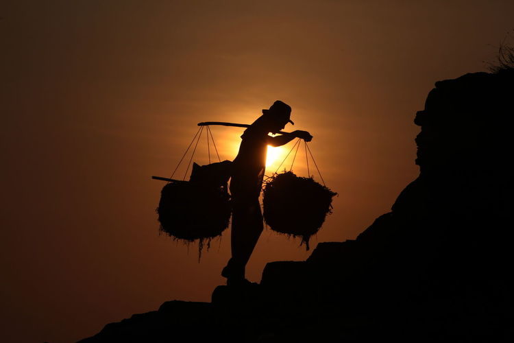 Silhouette Man With Baskets Carrying On Shoulders Against Sky During Sunset