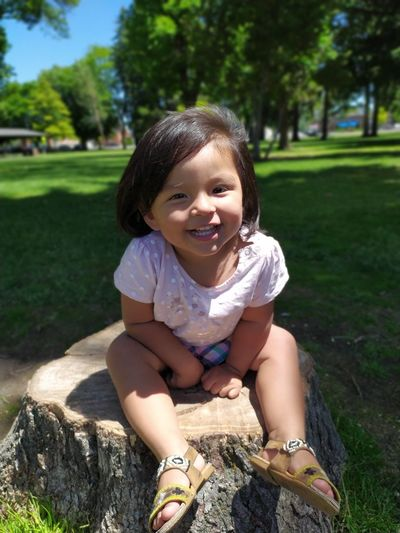Portrait of smiling baby girl sitting on tree stump in park