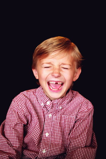 Laughing Boy Black Background Boy Boys Casual Clothing Childhood Cute Elementary Age Funny Happiness Happy People Headshot Missing Tooth Person Portrait Real People Red Smiling Teeth Waist Up