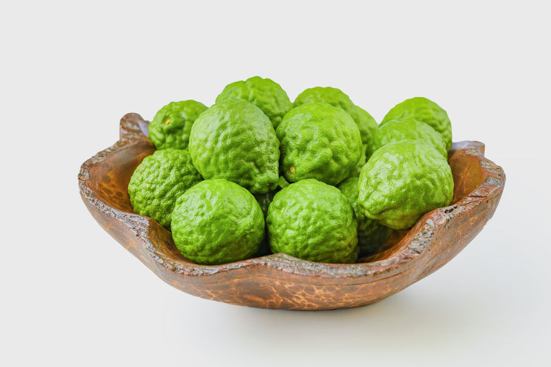 Close-up of green fruit on table against white background