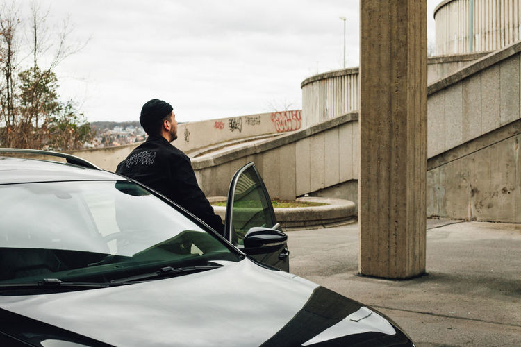 Man standing on car against sky