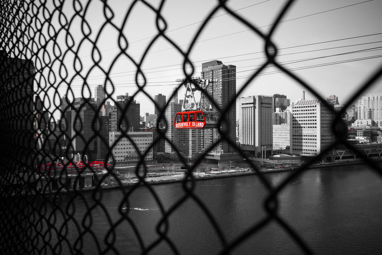 Roosevelt Island Tram through a fence Commuting New York New York City POV Roosevelt Island Tram Tram Transportation Barrier Black And White Chainlink Fence City Cityscape Fence Point Of View Skyscraper Transportation Water