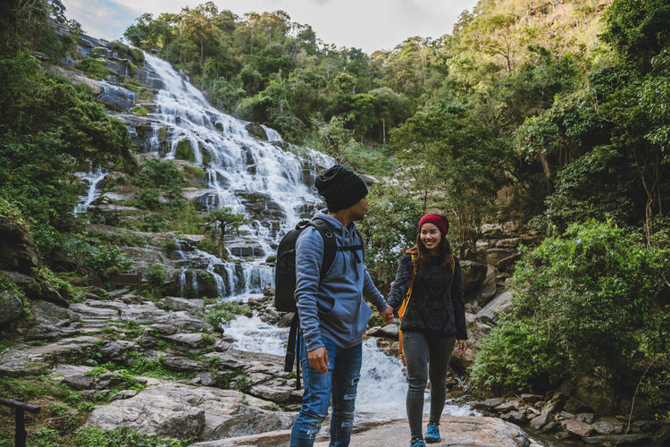 Smiling woman with friend standing by waterfall in forest
