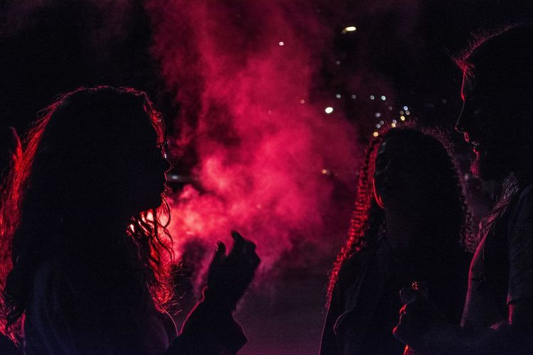 People illuminated by red light at night