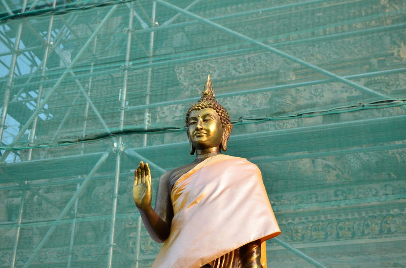 Buddha statue against scaffolding on building