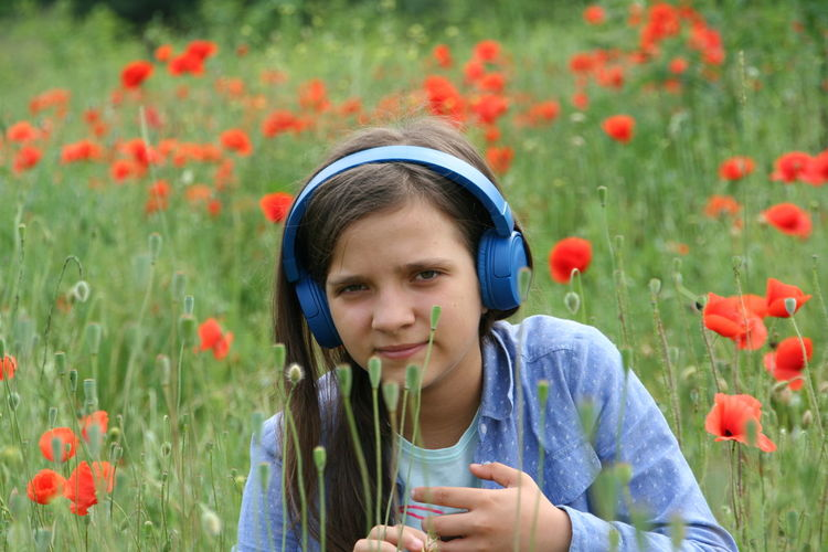 Portrait Of Girl Listening Music On Field With Red Flowers