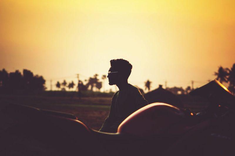 Silhouette man looking away during sunset