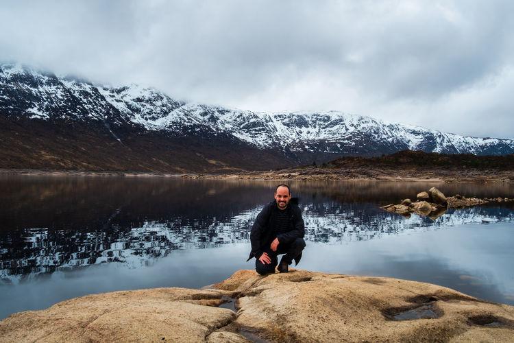 Full length portrait of man on rock by lake against sky