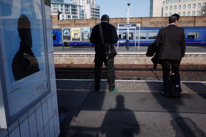 Rear view of men standing on sidewalk in city