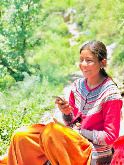 Smiling young woman using smart phone outdoors