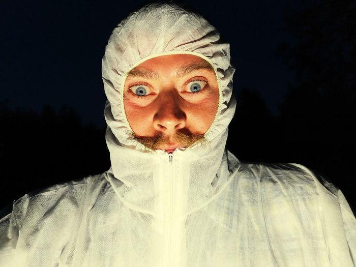 Portrait of man wearing white hooded shirt against black background