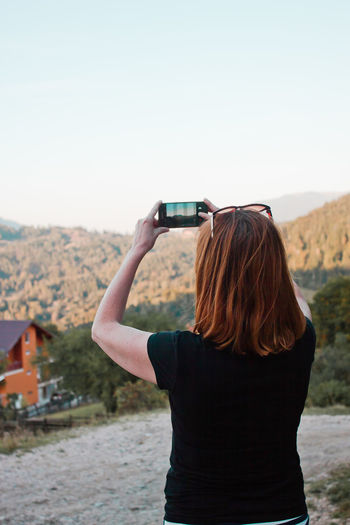 Girl taking a picture Activity Adult Communication Focus On Foreground Hair Hairstyle Holding Leisure Activity Lifestyles Mobile Phone Nature One Person Outdoors Photographing Photography Themes Portable Information Device Real People Rear View Sky Smart Phone Technology Wireless Technology Women