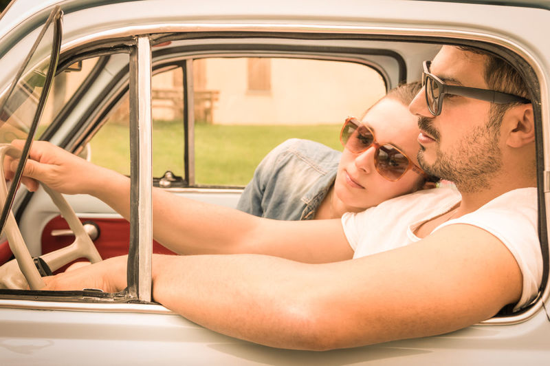 Couple Traveling In Car Seen Through Vintage Car