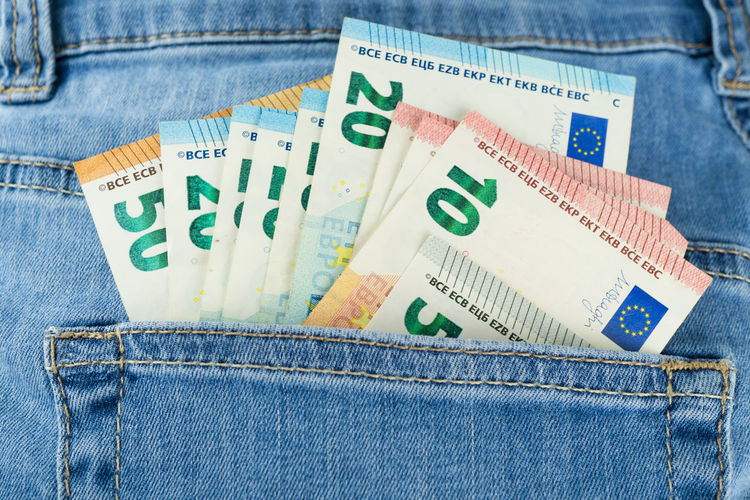 Close-up of paper currencies in jeans pocket