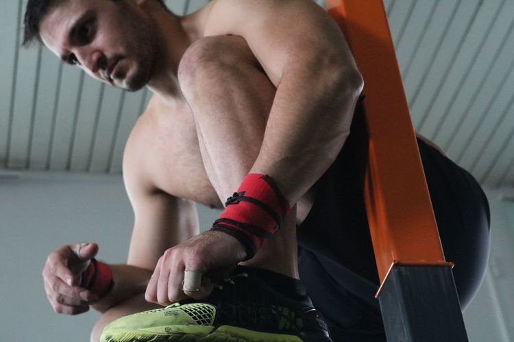 Midsection of shirtless man tying shoe lace