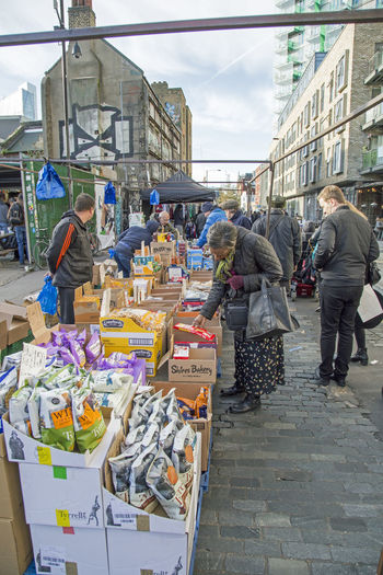 November 2017, Brick Lane, London England, A woman inspects goods on a stall at a street market. Street Market Adult Building Exterior Built Structure City Day Group Of People Inspecting Large Group Of People Market Men Outdoors People Real People Sky Women