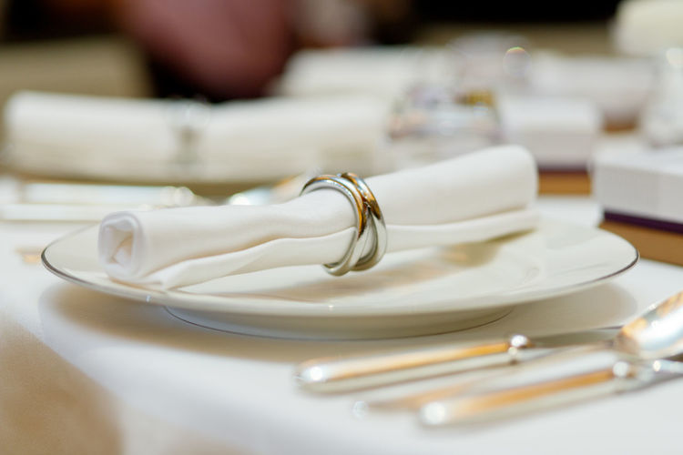 The white napkin nicely folded on the plates, serving a celebratory banquet Table Indoors  Plate White Color Selective Focus Close-up Setting Food And Drink Place Setting No People Focus On Foreground Event Celebration Furniture Business Still Life Preparation  Restaurant Household Equipment Glass Crockery Luxury Clean Dining