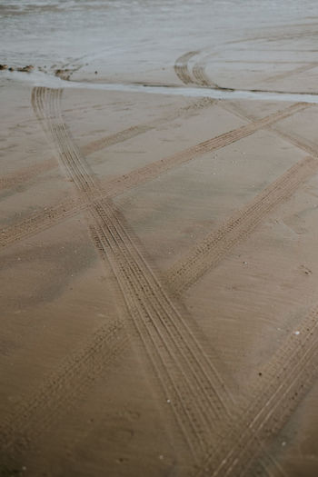 High angle view of tire tracks on beach