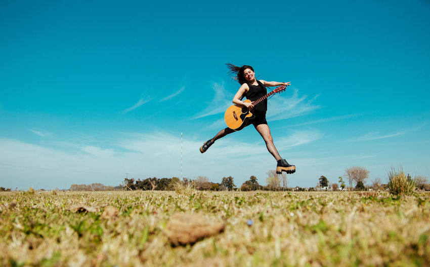Land Full Length Sky Jumping Mid-air One Person Motion Field Nature Plant Leisure Activity Day Lifestyles Young Adult Grass Running Vitality Blue Young Women Casual Clothing Outdoors Human Arm Surface Level Shorts