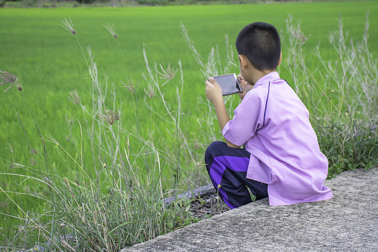 Asian boy holding a phone and sitting on the street Background the green rice fields. Adult App Asian  Attractive Background Beautiful Boy Business Casual Cell Cellphone Device Fun Game Green Guy Hand Happy Hold Internet Isolated Lifestyle Looking Mail Male Man Media Message Mobile Modern Nature One Online  Outdoor People person Phone Playing Portrait Road Smart Smartphone Social Student Summer Technology Teenager Using Video White