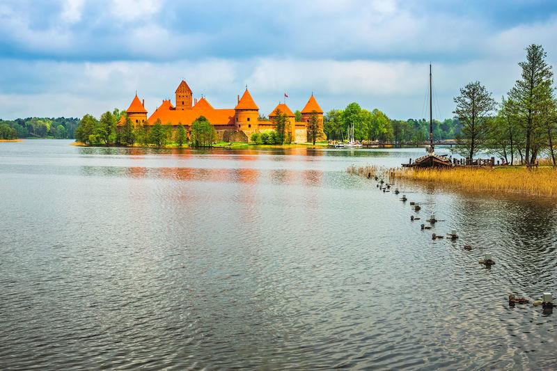 Trakai island castle amidst lake galve against cloudy sky