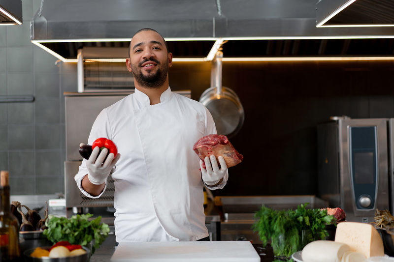 Portrait of chef holding meat and vegetable at kitchen