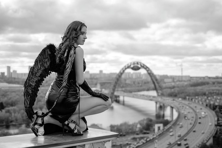 Woman wearing costume while sitting kneeling sky in city