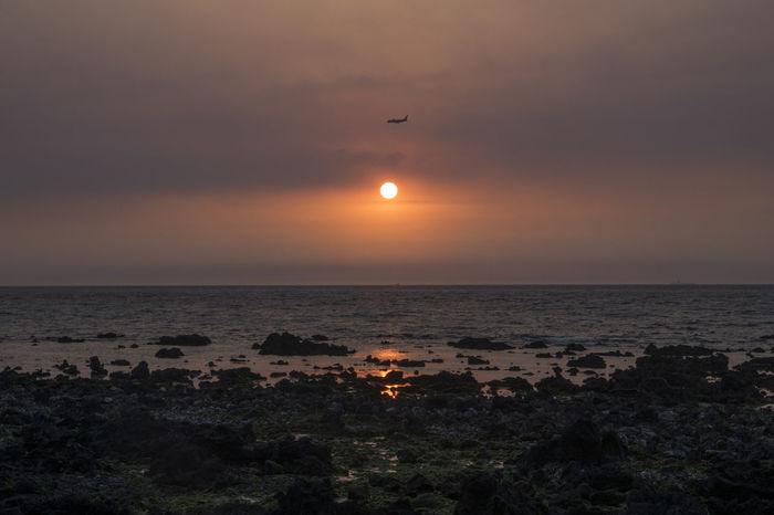 sunset in the coast of Jeju Island, South Korea JEJU ISLAND  Airplaine Beach Beauty In Nature Clear Sky Horizon Over Water Idyllic Illuminated Landscape Moon Nature No People Orange Color Outdoors Scenics Sea Silhouette Sky Sun Sunset Tranquil Scene Tranquility Water