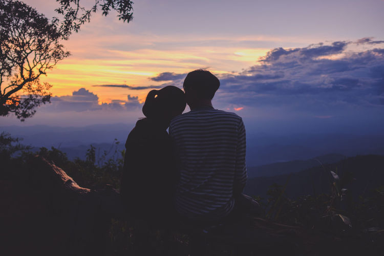 Rear view of silhouette couple sitting on mountain against sky during sunset