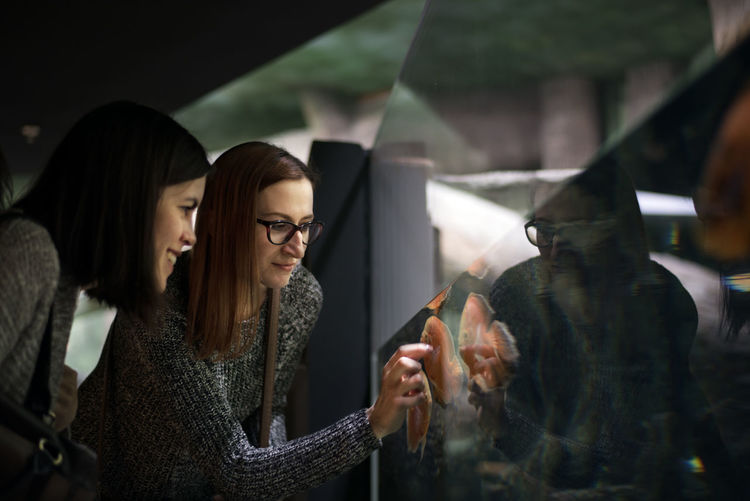 Female friends looking at fish swimming at aquarium