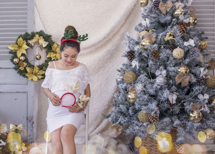 Pregnant woman sitting on chair by christmas tree at home