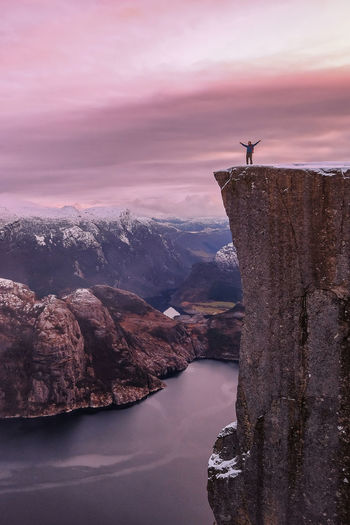 Man on cliff by fjord against sky during sunset